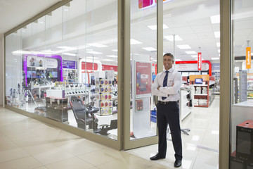 Portrait of smiling salesman standing in doorway of electronics store
