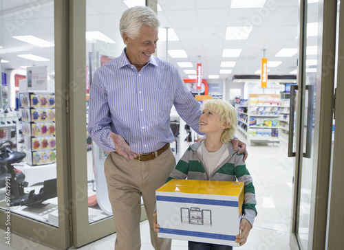 Smiling grandfather and grandson leaving electronics store with box