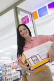 Portrait of smiling woman leaving electronics store with boxes