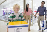 Portrait of smiling family leaving electronics store with boxes
