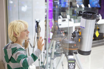 Smiling boy eyeing telescopes in electronics store window