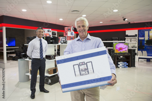 Portrait of senior man holding box in electronics store