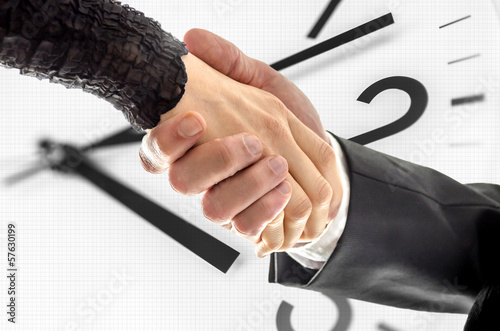Business handshake over white clock