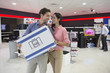 Smiling couple holding box in electronics store