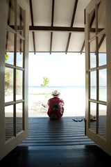 man sitting on decking with sea view
