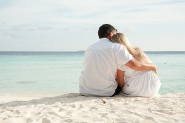 couple sittng on sand facing ocean
