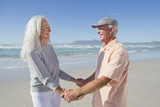 Happy senior couple holding hands on sunny beach