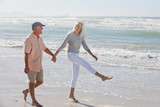 Senior couple holding hands and walking on sunny beach
