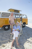 Senior couple drinking coffee on beach outside van