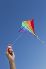 Boy flying multicolor kite in blue sky