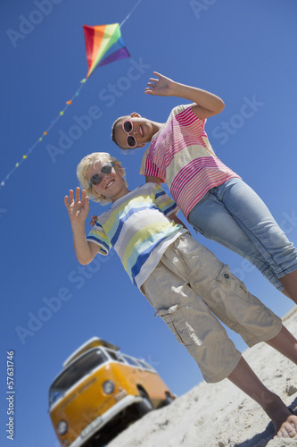 Portrait of happy brother and sister waving under kite with van in background