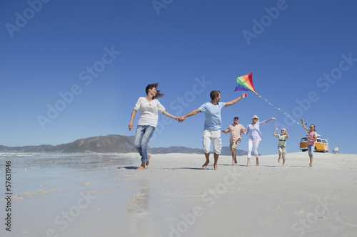Happy multi-generation family with kite running on sunny beach