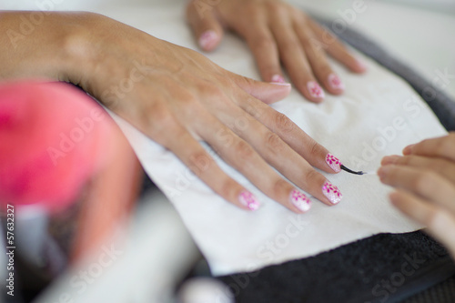 Nail technician applying fingernail polish to woman's fingernails