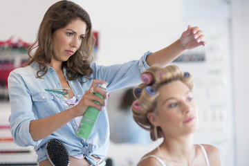 Hairdresser spraying hairspray on rollers in woman's hair at salon