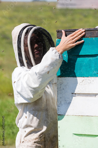 Female Beekeeper Working At Apiary