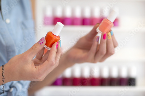 Close up of woman holding fingernail polish bottles in nail salon