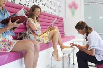 Woman getting pedicure at nail salon