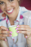 Close up portrait of woman holding tiny cup with flower design on manicured fingernails