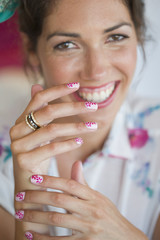 Close up portrait of woman with flower design on manicured fingernails