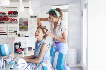 Hairdresser placing curlers in woman's hair at salon