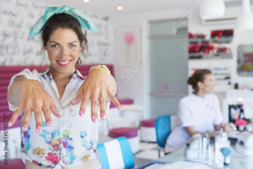 Portrait of smiling woman showing off manicured fingernails in nail salon