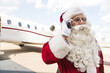 Santa Claus Communicating On Mobile Phone Against Private Jet
