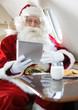 Santa Using Digital Tablet In Private Jet - 57633972