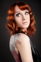 Рыжая девушка с татуировкой