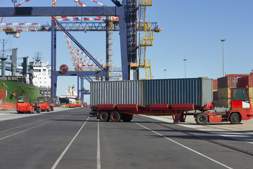 Truck moving cargo containers at commercial dock