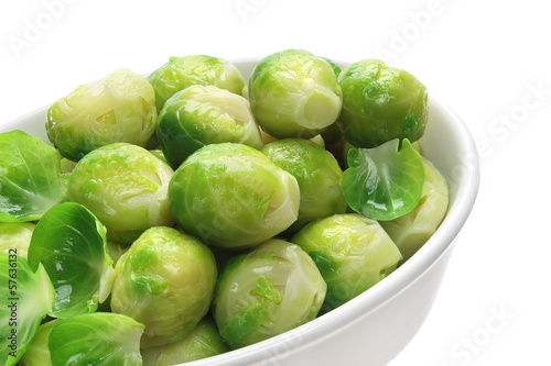 Cooked brussels sprouts in bowl on white background