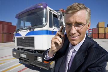 Portrait of smiling businessman talking on cell phone next to truck at commercial dock