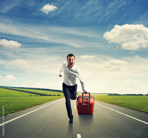 man with suitcase running on the road