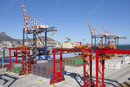 Cranes and cargo containers alongside moored cargo ship at commercial dock