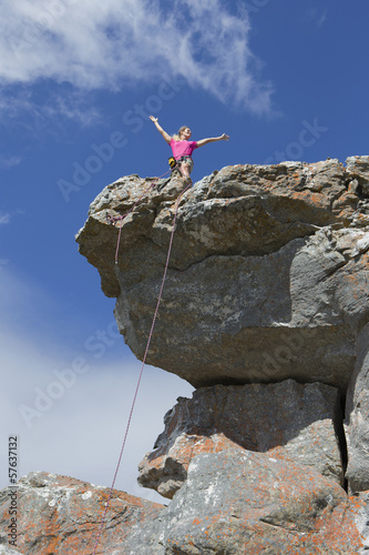 Female rock climber standing on top of rock with arms outstretched
