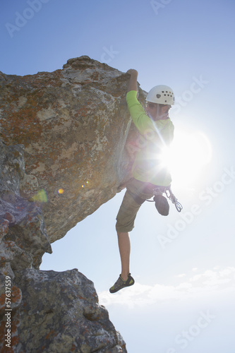 Sun shining behind male rock climber hanging from rock