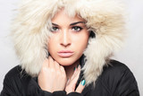 Fashion portrait of young beautiful woman with fur.fur hood
