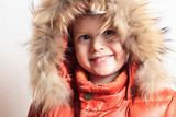 smiling child in fur hood and orange winter jacket.fashion boy
