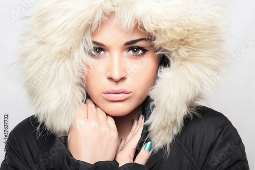 Fashion portrait of young beautiful woman with fur.fur hood