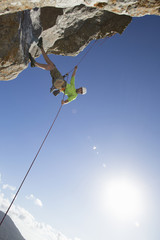 Sun shining behind male rock climber abseiling down rock face