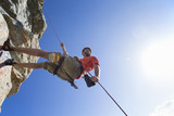 Male rock climber abseiling down rock face