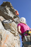 Woman watching male rock climber abseiling down rock face