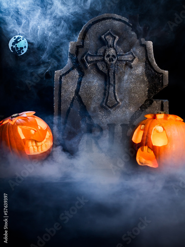 Halloween foggy night with pumpkins, tombstone, moon and bat.