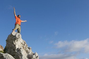 Male rock climber standing on top of rock with arms outstretched