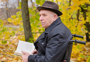 Pensive man reading outdoors in autumn