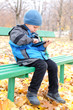 Little boy reading a tablet computer in park