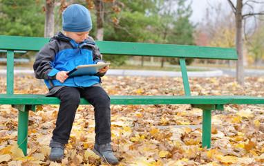 Little boy reading a tablet computer