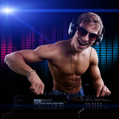 Sexy DJ macho is playing disco music in headphones