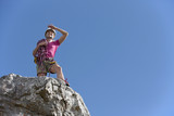 Female rock climber looking at view from on top of rock