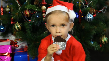 Child Dressed in Santa Claus Eating Chocolate by Christmas Tree