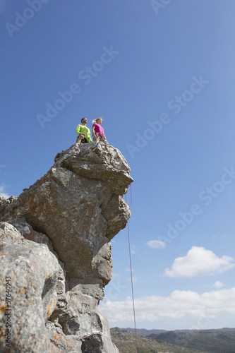 Rock climbers looking at view from on top of rock